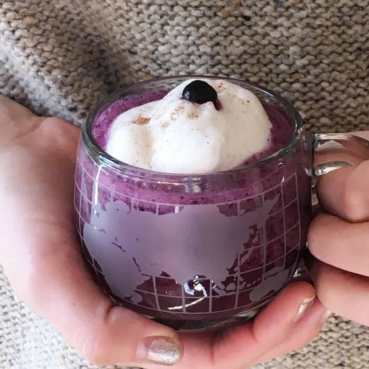 hands holding blueberry latte