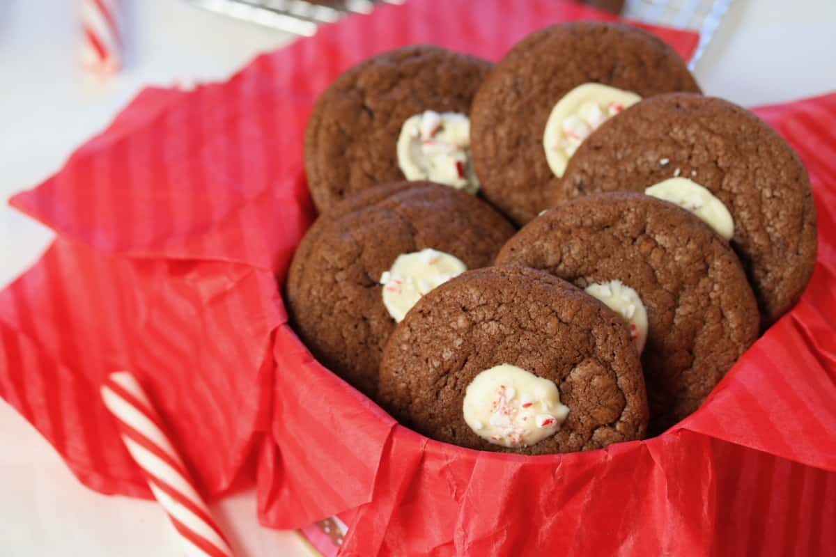 good grief baking therapy includes peppermint stick cheesecake stuffed cookies in a cookie tin lined with red paper and a peppermint stick