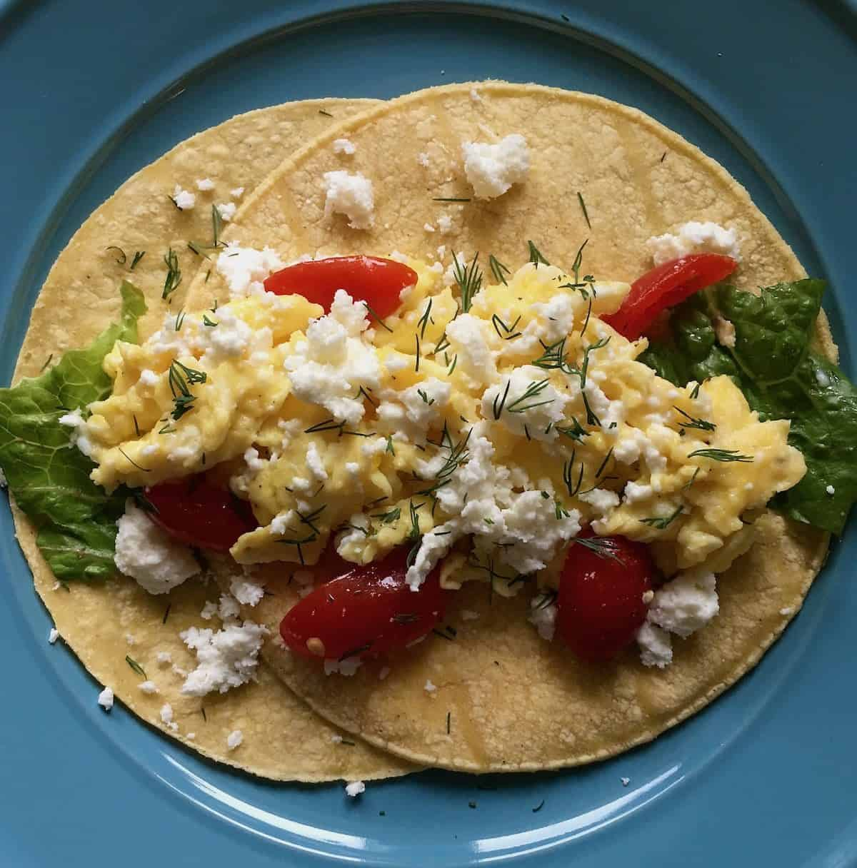 tortillas topped with eggs, cheese and tomatoes